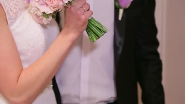 Bride holding wedding bouquet and laughs