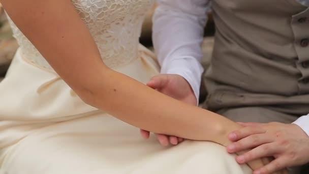 Novomanželé jemně hladí navzájem ruce