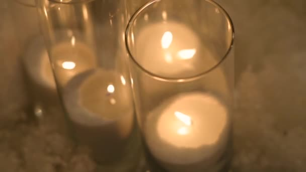 Burning candles in glass candlestick