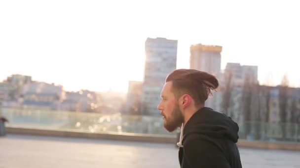 Muž se spouští před západem slunce ve městě