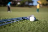 Golfový míček a golfového klubu na zelené trávě