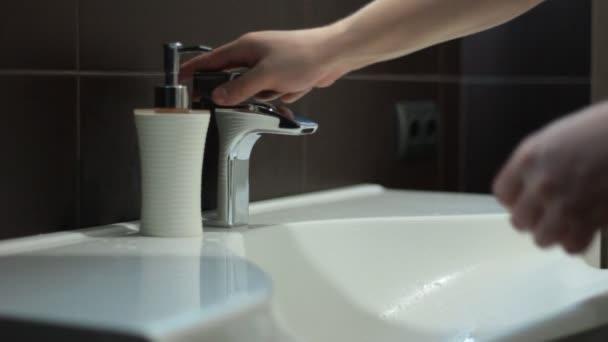 Muž myje ruce v koupelně