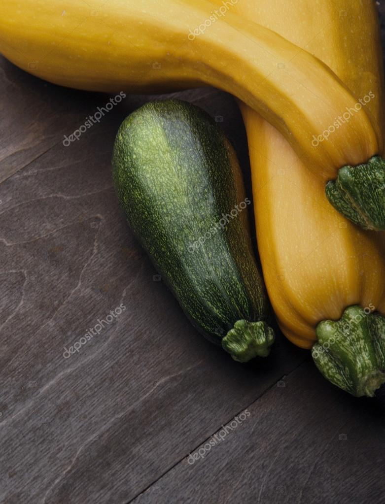 Two yellow big and medium small green zucchini on wooden table ...