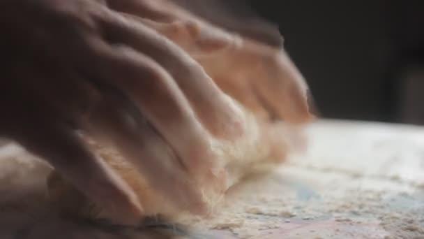 Baker ruce hnětení těsta v mouce na stole