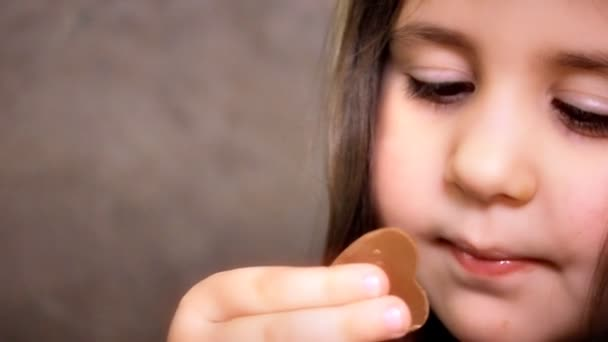 Little Girl Face Close Up With Long Hairs is Looking in Camera and smiling. Little beautiful girl taste chocolates with gusto.