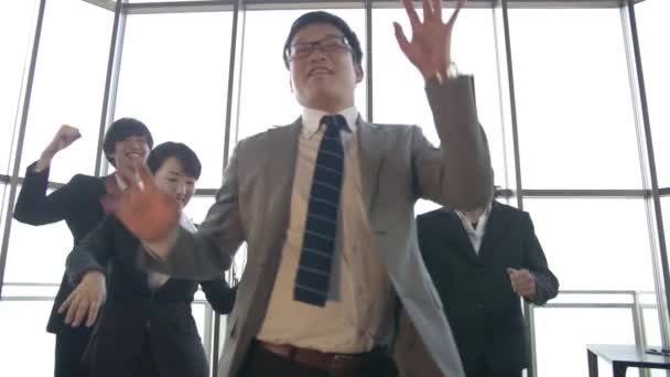 Japanese boss and his team celebrate by dancing in the office slow motion