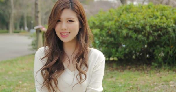 Atraktivní japonská dívka, která nosí bílé úsměvy pro fotoaparát, posuvné shot