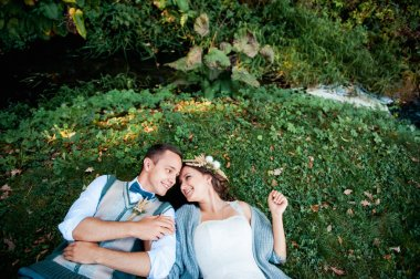 beautiful couple lying and hugging near a river