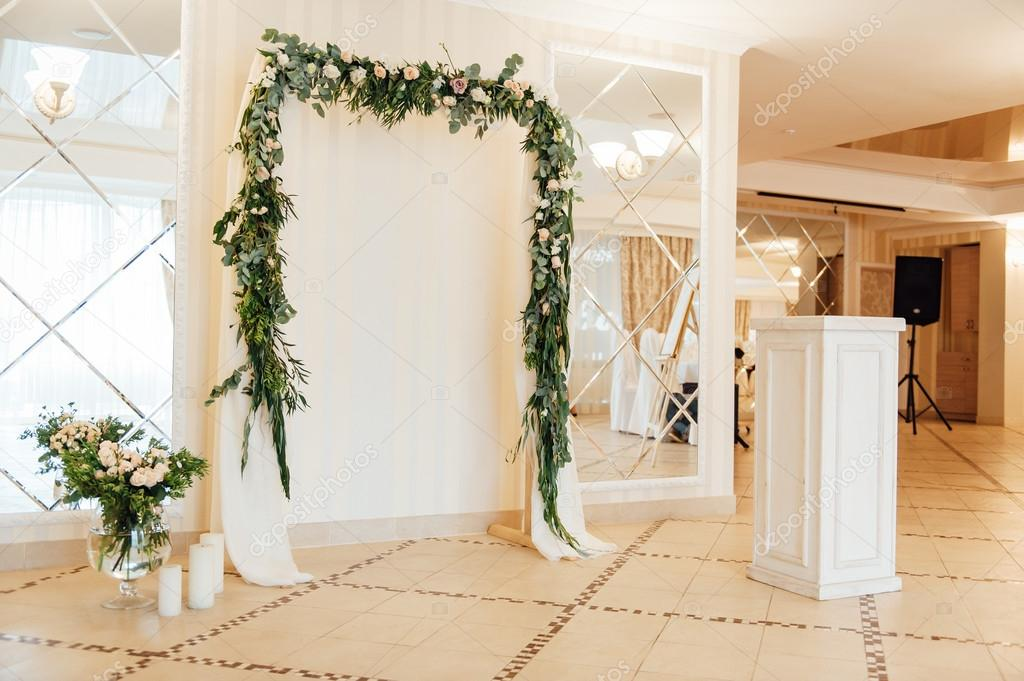White wedding arch decorated with flower indoor stock photo beautiful white wedding arch decorated with pink and red flowers indoor photo by rubanoki junglespirit Choice Image