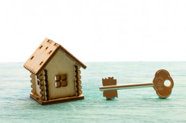 toy wooden model house as symbol family and love concept  on sunny old blue wooden background buying a house, mortgage, repair, stability, the keys