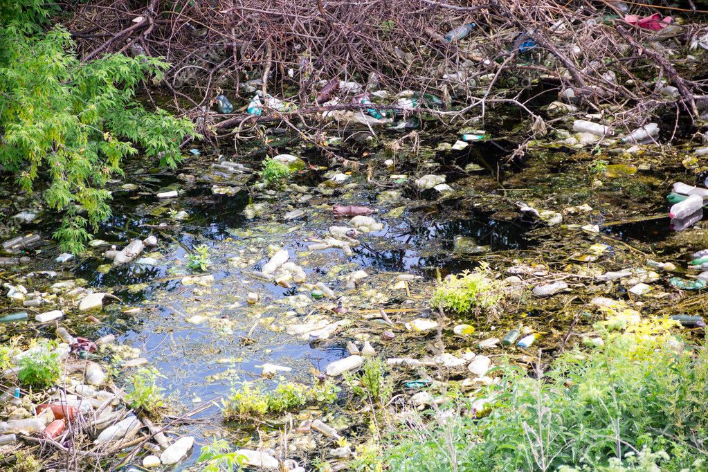 Illegal bulk waste discarded. Landfill in the river. polluted environment.  problem concept