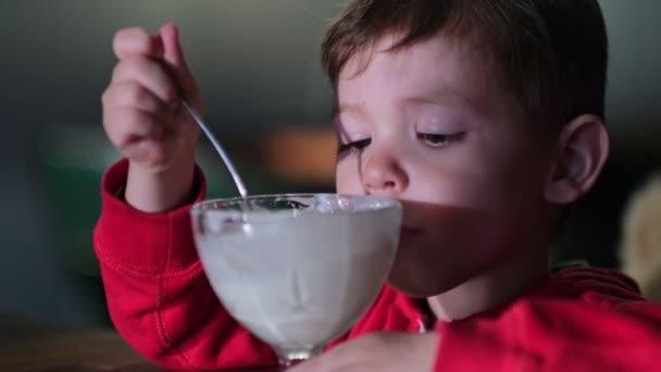 Kleiner Junge isst Eis im Café. Niedliches Kind, das in einem Restaurant Vanillejoghurt genießt. Zeitlupenaufnahme.
