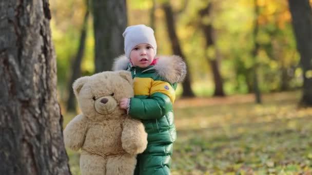 kleiner Junge beim Spielen mit einem Plüschtier im Park. Lustiges Baby in warmer Daunenjacke und seinem Teddybär. Nahsicht. Zeitlupenvideo. Archivbild