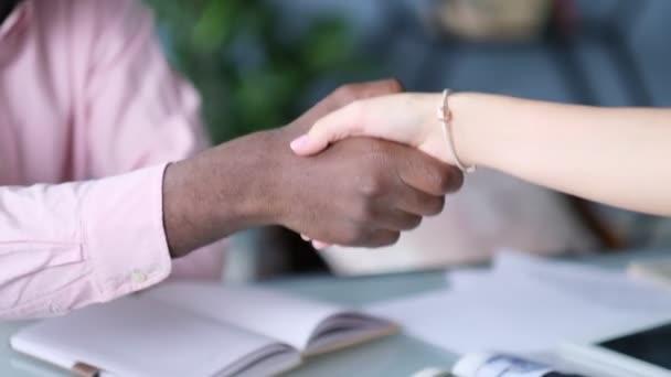 Afroameričtí obchodníci si potřásají rukou s bělošskou podnikatelkou. Detailní záběr Afroameričana, jak si potřásá rukou se svou kolegyní v úřadu. Koncept setkání