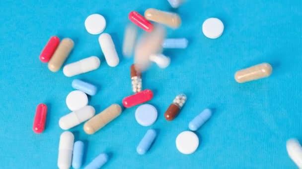 Spousta prášků na léky. Pozadí z barevných pilulek a kapslí. Léky na předpis. Zpomalené video. stock záběry
