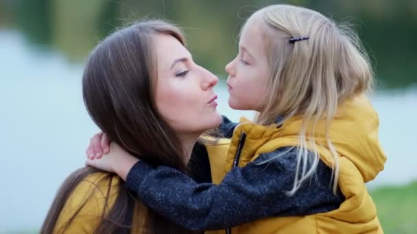 Daughter kissing mother on nature. Beautiful young woman and her charming little daughter are hugging and smiling. Daughter hugging mother on nature.