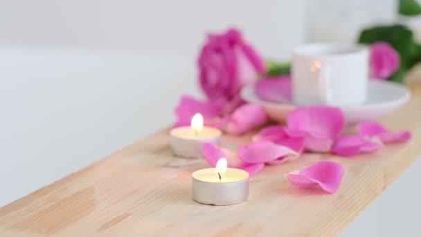 Wunderschöner Wellnessbereich mit rosa Kerze und Blumen auf hölzernem Hintergrund. Konzept der Kurbehandlung im Salon. Atmosphäre der Entspannung, Gelassenheit und des Vergnügens. Luxus-Lebensstil.