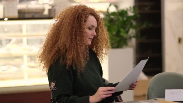 élénk vörös hajú nő ül egy asztalnál egy kávézóban, és kiválaszt egy ételt az étlapról. Lassított felvétel. készletfelvétel