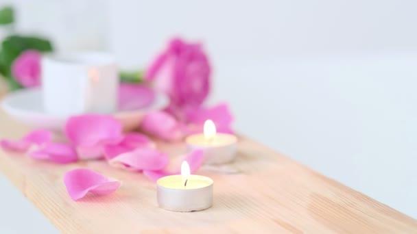 Krásné lázeňské prostředí s růžovou svíčkou a květinami na dřevěném pozadí. Koncepce lázeňské léčby v salonu. Atmosféra odpočinku, klidu a potěšení. Luxusní životní styl.