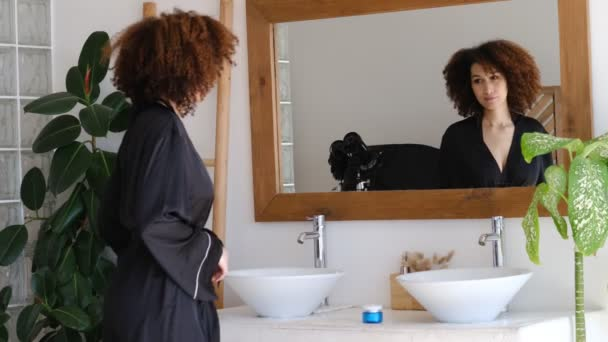Beautiful African American woman look in mirror enjoy healthy clean soft moisturized hydrated skin care admire herself feel proud narcissistic. Female looking at face in mirror.