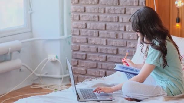 atraktivní žena sedí na posteli a pracuje u notebooku