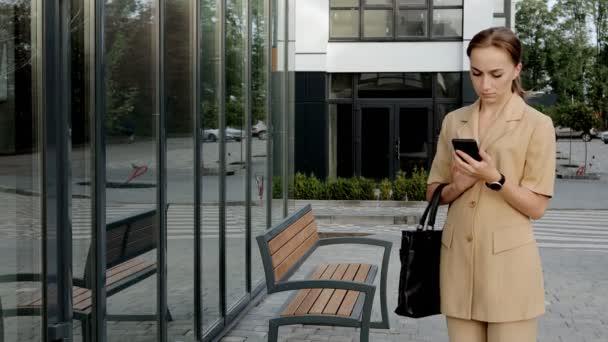 Felnőtt kaukázusi magabiztos fiatal üzletasszony beszél telefonon kívül közel Modern irodaház