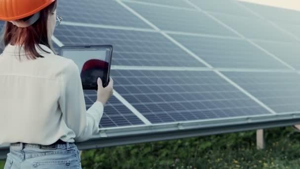 Schöne junge Ingenieurin steht in der Nähe von Sonnenkollektoren im Freien, Green Energy Concept