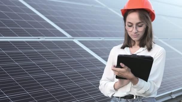 Inspektor Ingenieurin Frau mit digitalem Tablet arbeitet in Solarmodulen Stromfarm, Photovoltaik-Zellpark, Green Energy-Konzept