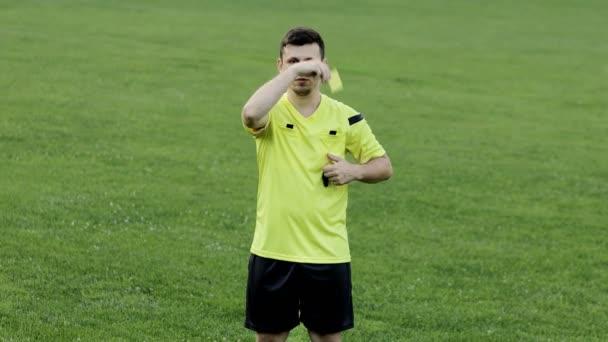 Fotbalový rozhodčí ukazující žlutou a červenou kartu, odstraní hráče. Pojetí sportu, porušení pravidel, ofsajd.