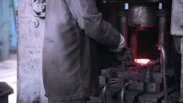 Arbeiter arbeitet mit automatisierter Metallbearbeitungsmaschine in einer Metallschmiede.