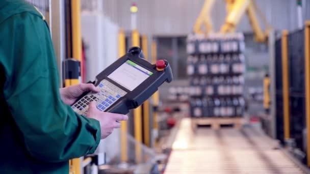 Pracovník s průmyslovými konzole, vzdálené pracuje s robotické rameno načítání a kompletace výrobků