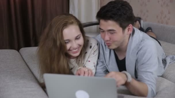 Usmívající se pár s přenosným počítačem doma. Technologie, domov, rodina koncept