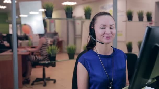 Frendly woman talking on the headset in a bright clean office, call center.
