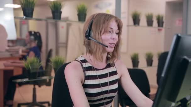 Frendly žena mluvila na sluchátkách v kanceláři, call centrum