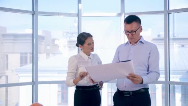 Obchodník a žena, inženýři pracující v jasně čisté kanceláři. Diskuse o stavebním projektu, plánu, výkresu, schématu.