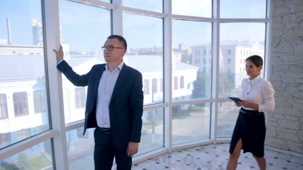 Üzleti, építészeti és irodai koncepció. Két sikeres üzletember vitassa meg a tablettát a tiszta, fényes irodában a panoráma ablak közelében.