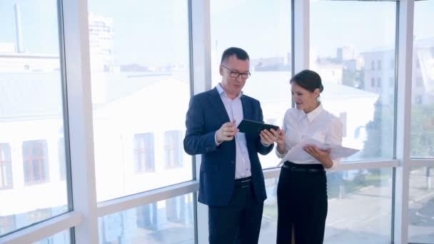 Obchodní, architektonická a kancelářskou koncepci. Dva úspěšní podnikatelé diskutují o projektu na tabletu v čisté jasné kanceláři blízko panoramatického okna.