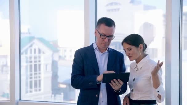 Business, architecture and office concept. Two successful businessmen discuss project on tablet in clean bright office near panoramic window.