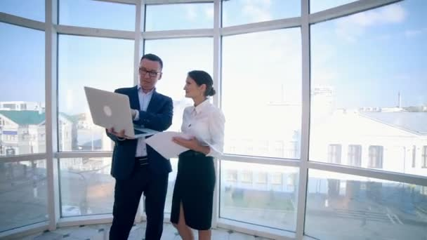 Businessmen man and woman discuss work project in a modern office building near clean panoramic window. Business concept. Steadicam shoot.
