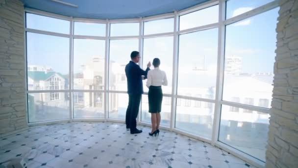 Podnikatelé a ženy diskutují pracovní projekt v moderní kancelářské budově nedaleko čistého panoramatického okna. Obchodní koncepce. Sestřelí ze steadicamu.