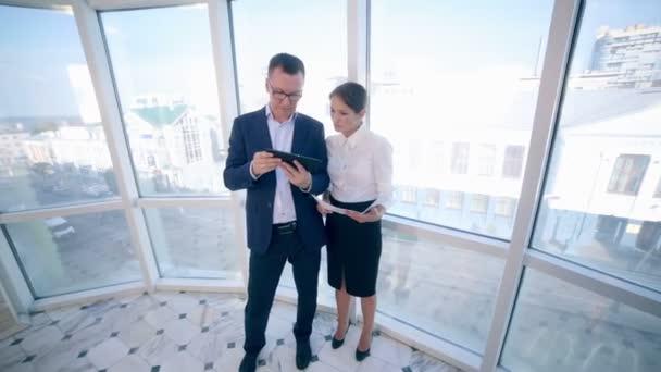 Kolegové o projekt na tabletu v čisté světlé kanceláři panoramatická okna. Obchod, koncepce týmové práce.