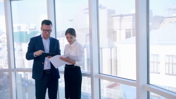 Kollegen besprechen Projekt auf Tablet im sauberen, hellen Büro in der Nähe des Panoramafensters. Business, Teamwork-Konzept.