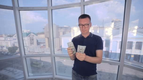 Sebevědomý, usmívající se muž inventur a vykazují peníze, nás dolary do kamery.
