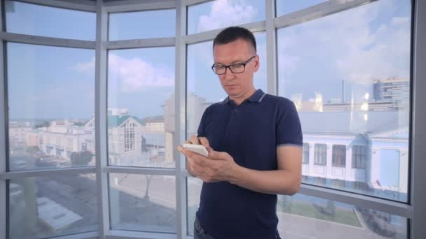 Sebevědomý, vážný muž počítání peněz, nás dolarů pomocí smartphonu