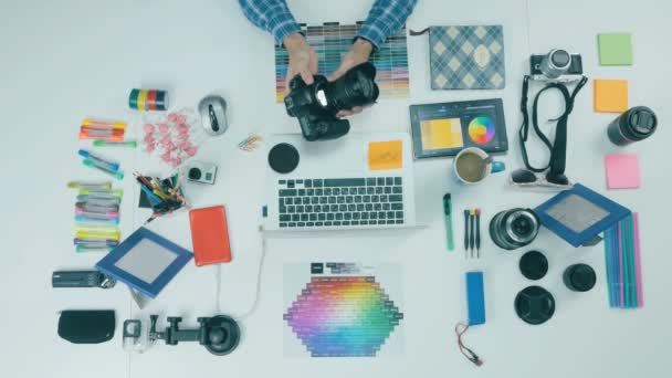 Unrecognizable creative photographer working at his workplace. Top view.
