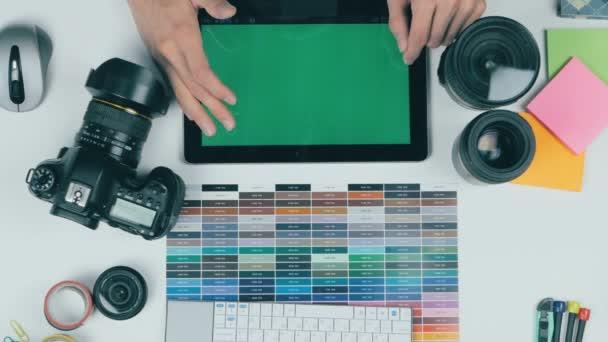 Tablet z výše. K nepoznání kreativní návrhář pracující s tabletem na jeho pracovišti. Freen obrazovky na tabletu.