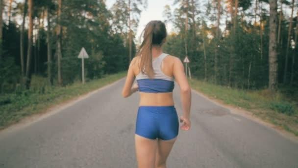 Sportovní youg žena běhání v parku. Zpomalený pohyb. Steadycam shot