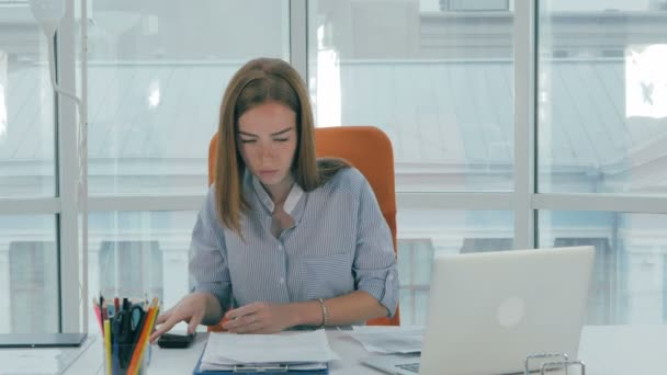 Young busy attractive business woman working in modern office. Timelapse.