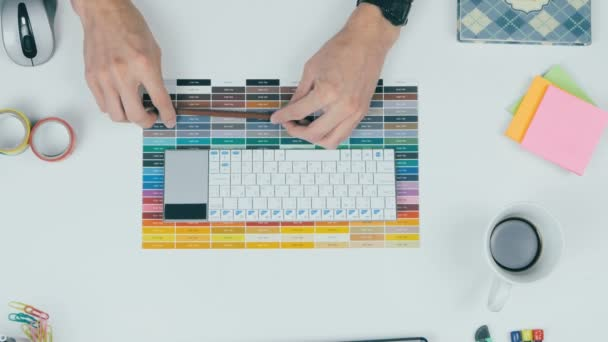 Unrecognizable creative designer working with colors on his workplace. Top view.