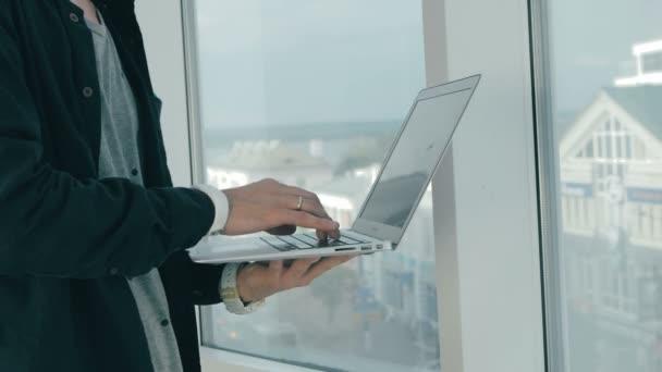 K nepoznání muž pracující na notebooku panoramatická okna v moderní kanceláři. Panoráma města na pozadí